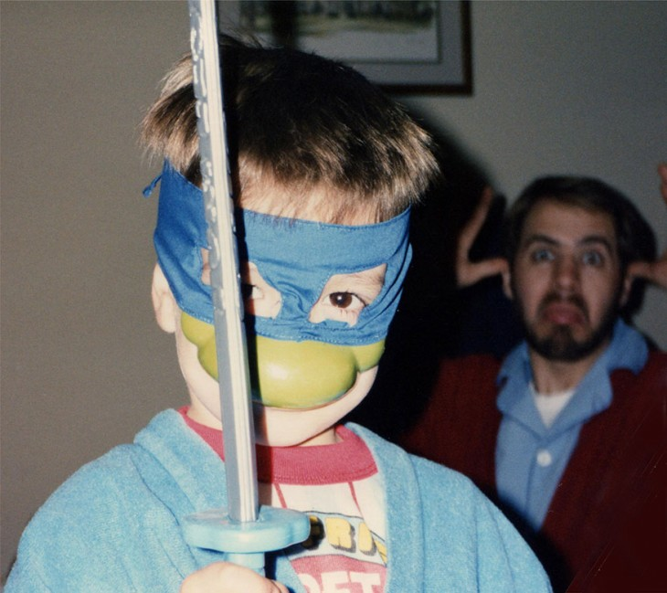 niño con mascara de las tortugas ninja y una espada, atras su padre haciendo caras