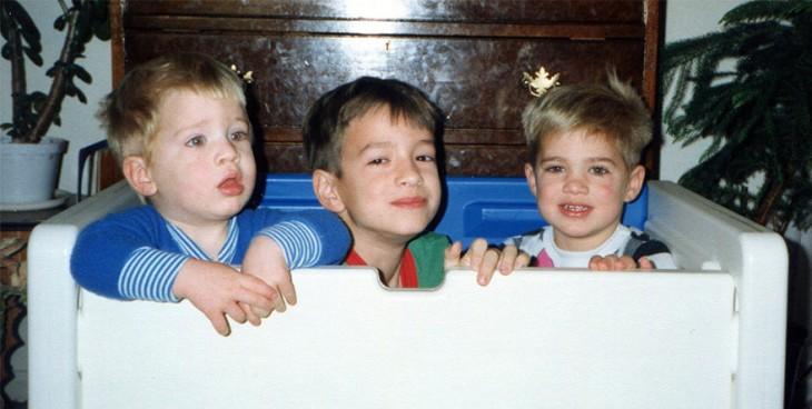 tres pequeños niños dentro de un cuadro de plastico