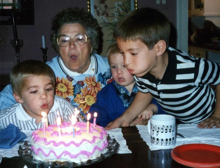 niño soplnado las velas de su pastel de cumpleaños acompañado de su abuela