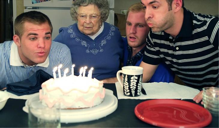 joven soplando las velas de su pastel de cumpleaños acompañado de sus otros dos hermanos y abuela
