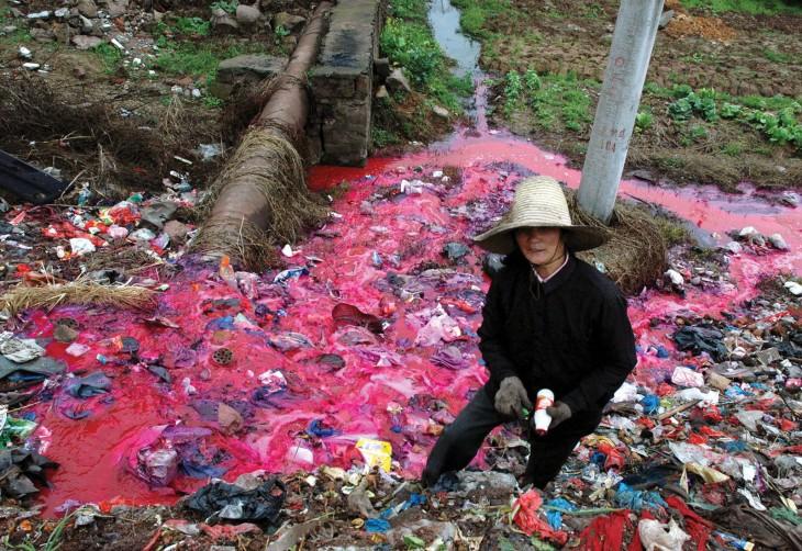 Mujer juntando botellas de plástico en un río contaminado de color rojo en china