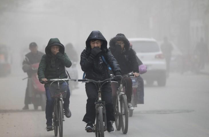 personas andando en bicicletas en medio de la polución en las calles de China