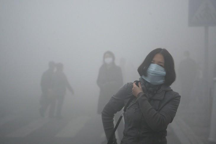 Chica camina con un barbijo por las calles de Beijin, donde la polución es 40 veces mayor a los estándares internacionales de seguridad