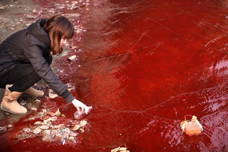 Reportera toma una muestras de agua roja contaminada del río Jianhe