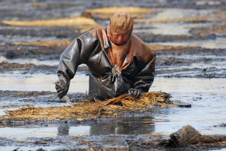 Trabajador intentando quitar el petroleo del agua, Dalian, Liaoning