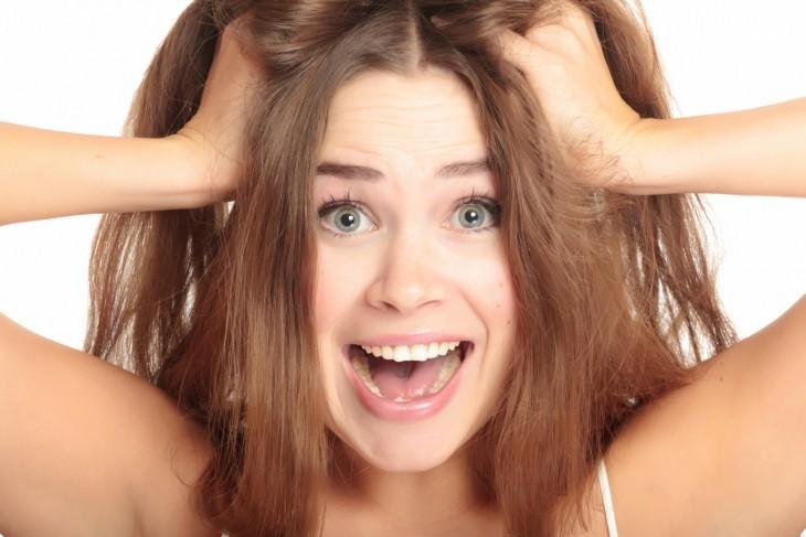 mujer gritando estirandose el cabello con las manos