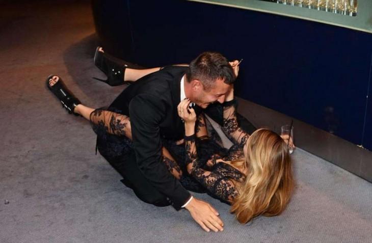 mujer con vestido negro se cae con un hombre