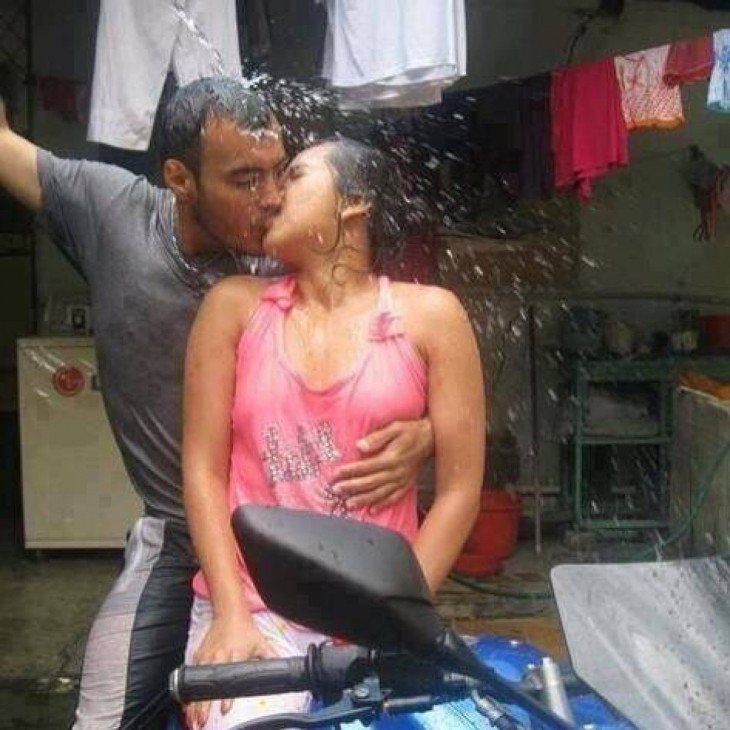 Dos enamorados en una moto bajo el chorro de agua