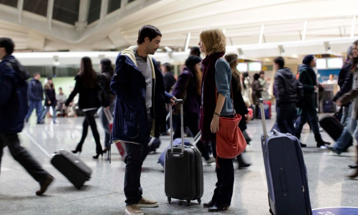 Pareja de novios en un aeropuerto repleto de gente