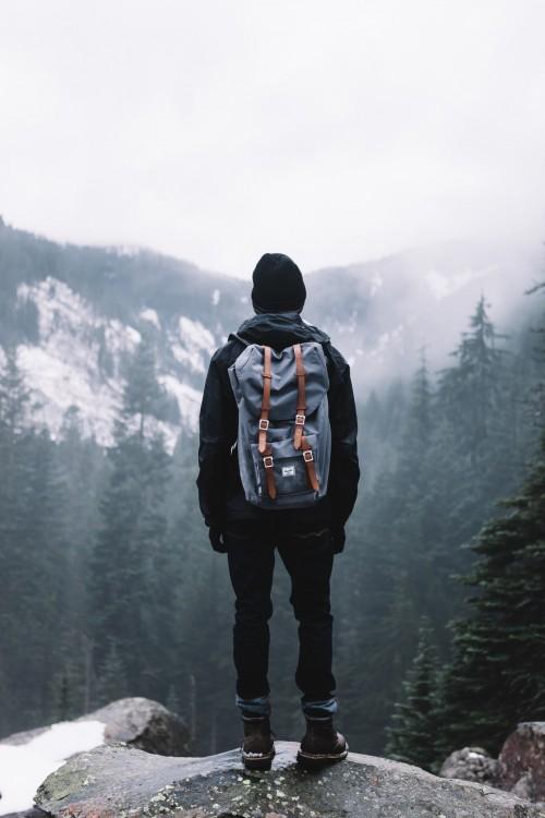 Hombre parado en la cima de una montaña