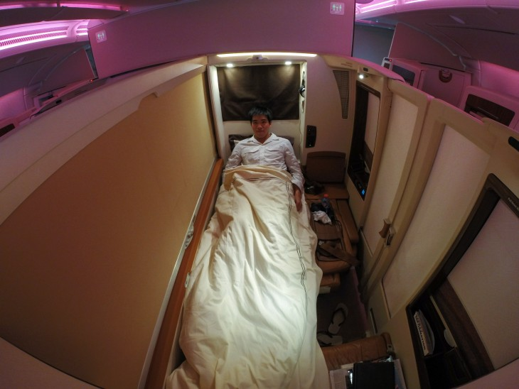 hombre durmiendo en 1 clase de aerolinea singapour