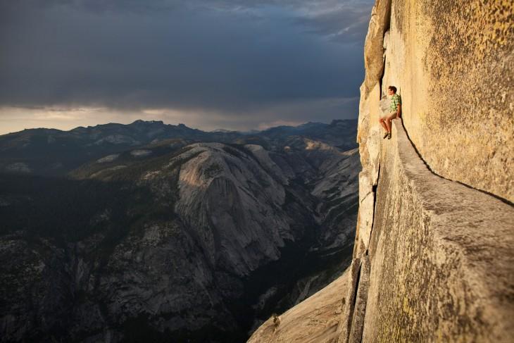 hombre sentado en las alturas en un risco
