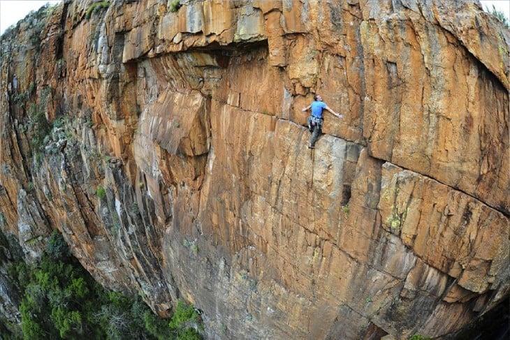 hombre escalando riscos