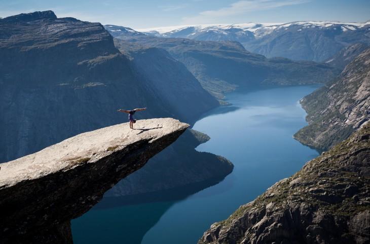 hombre arriba de una roca viendo lago