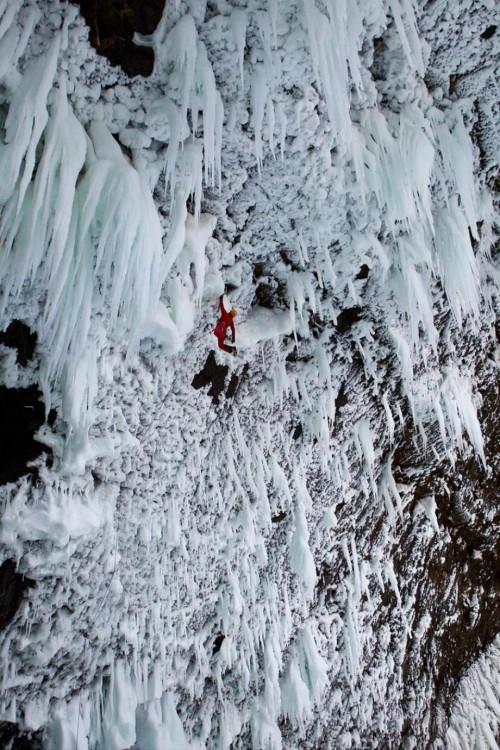hombre escalando risco con hielo