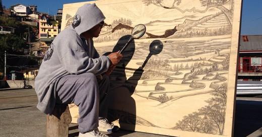 artista usa lupa para crear obras de arte