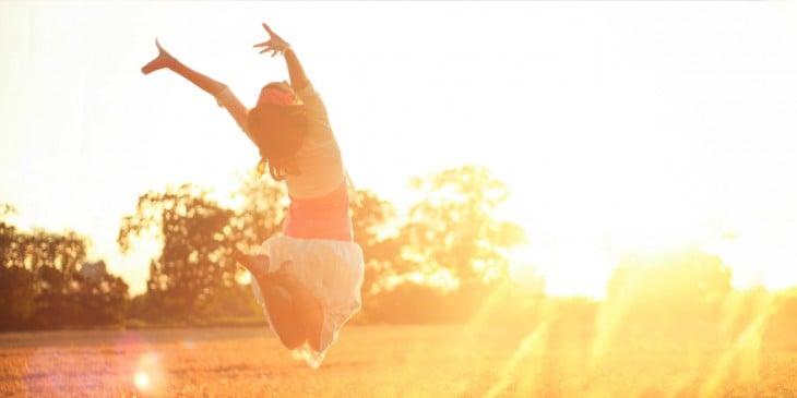 Mujer saltando de Felicidad en una puesta de Sol