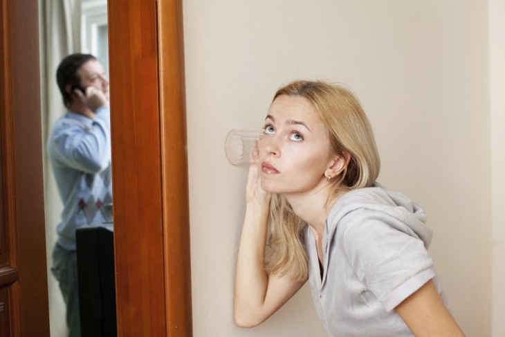 mujer con un vaso escuchando la conversacion de un hombre