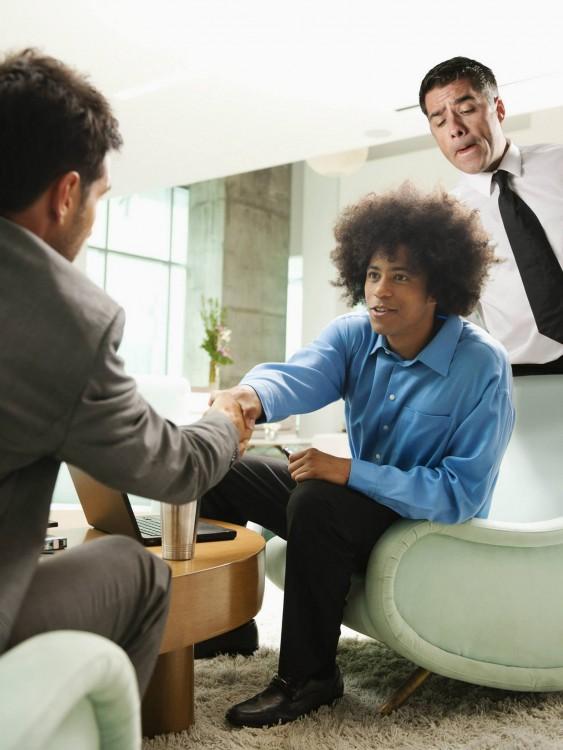 dos hombres sentados hablando y otro interrumpiendo