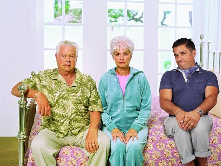 pareja de abuelos sentados en la cama con otro hombre al lado