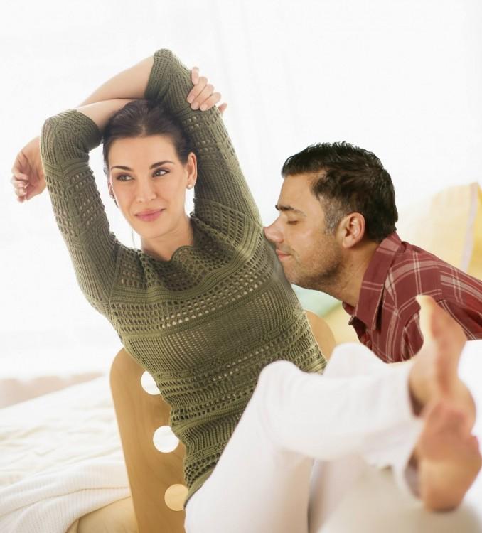 mujer sentada estirando los brazos hombre oliendola