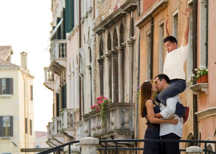 hombre besando a mujer en la calle con otro arriba