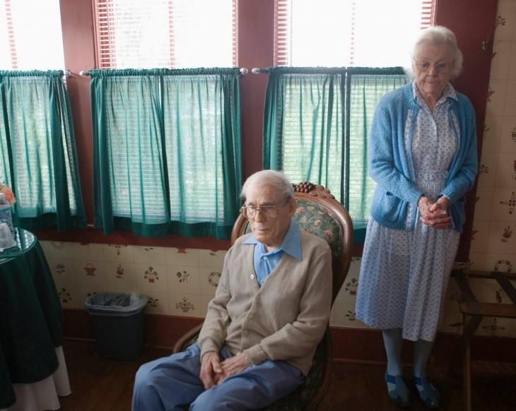 pareja de abuelos en el living y un hombre aspirando