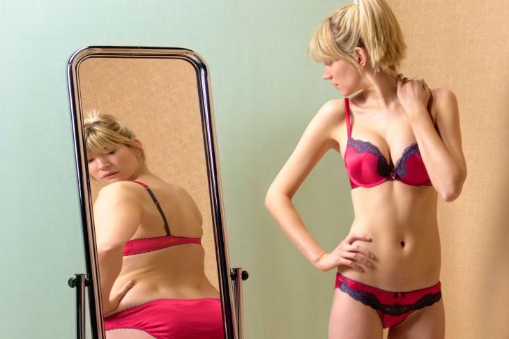 mujer que se ve en el espejo y cree que esta gorda