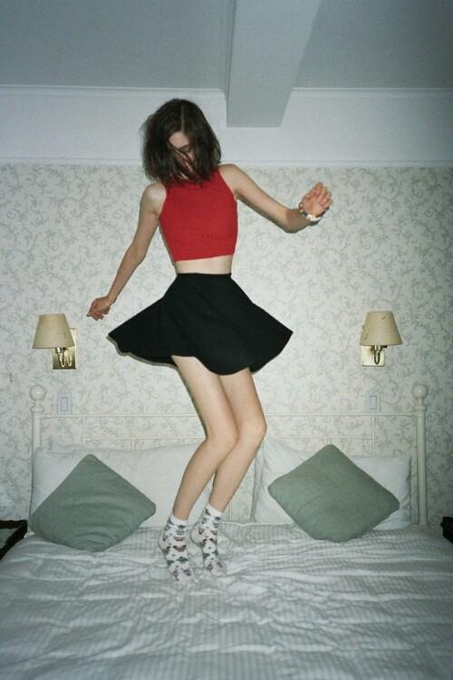 mujer brincando con una falda sobre la cama