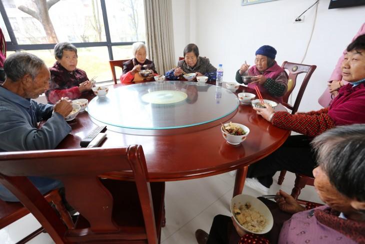 mesa con viejos chinos comiendo Xiong Shuihua