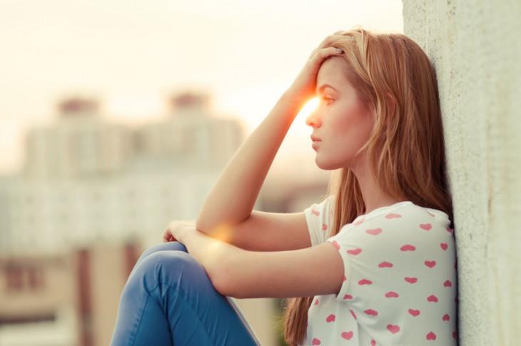 mujer tocandose la cabeza porque pensando durante el atardecer