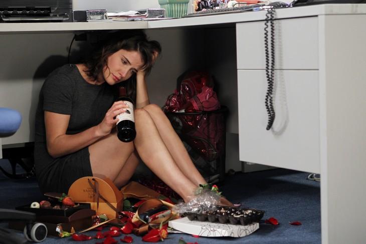 mujer triste comiendo chocolates y tomando vino