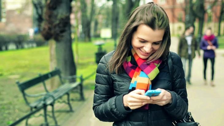 mujer que esta en un parque sonriendo al ver su celular