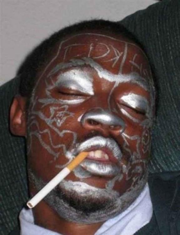 duerme ebrio, y le pintan la carade plateado y le ponen un cigarrillo