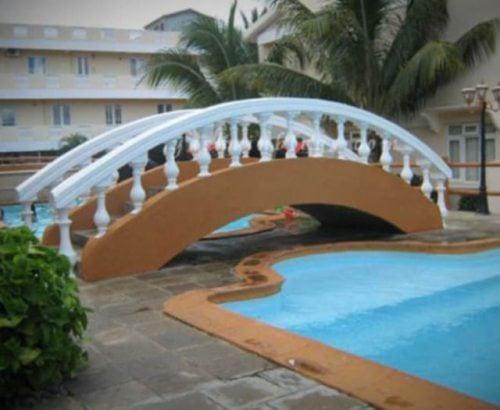 puente que pasa sobre el pasillo junto a una piscina
