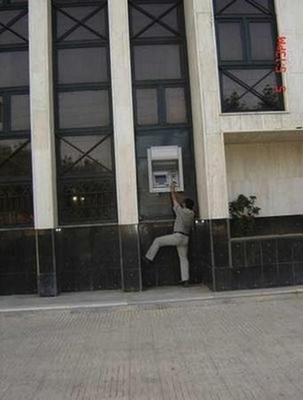 hombre intentando sacar dinero de un cajero automático que esta demasiado alto