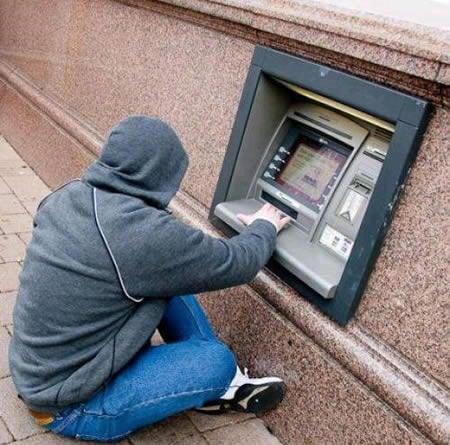 hombre sacando dinero de un cajero automático sentado en el suelo