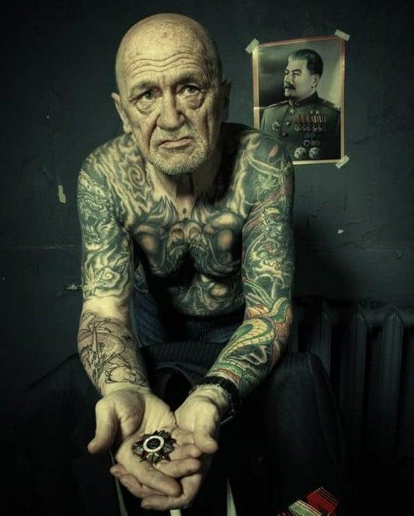 hombre sentado sin camisa con tatuajes en todo el cuerpo