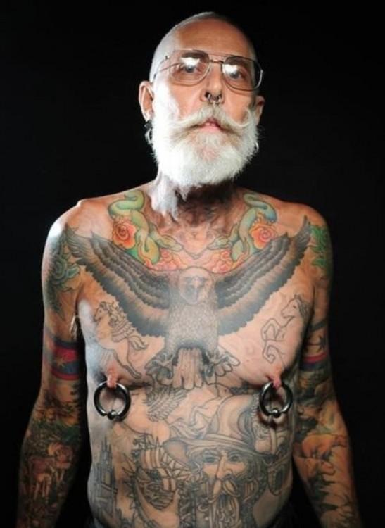 hombre de edad avanzada con tatuajes en todo el cuerpo y perforación en los pezones