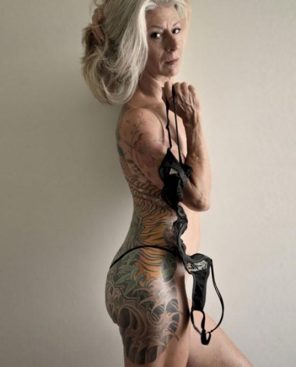 mujer adulta enseñando sus tatuajes del cuerpo