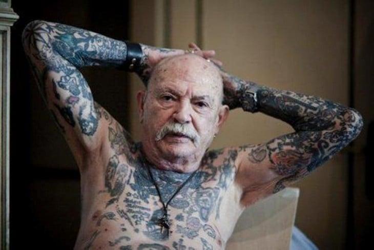 Anciando mostrando sus tatuajes del pecho y brazos