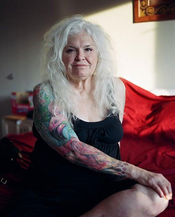 Mujer adulta de cabello blanco con tatuajes en los brazos