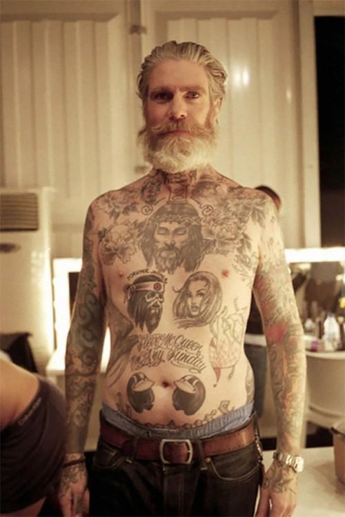 Hombe con tatuaje en el torso, cuello y brazos