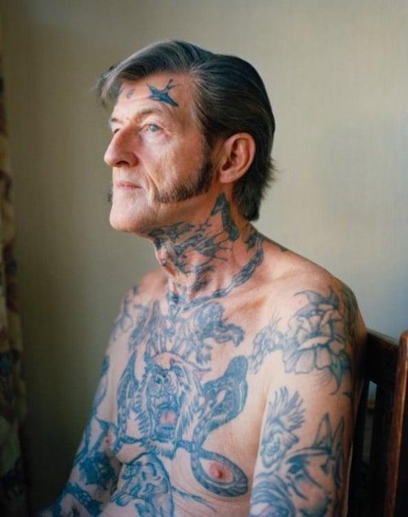 Hombre mayor con tatuajes en todo el cuerpo y la cara
