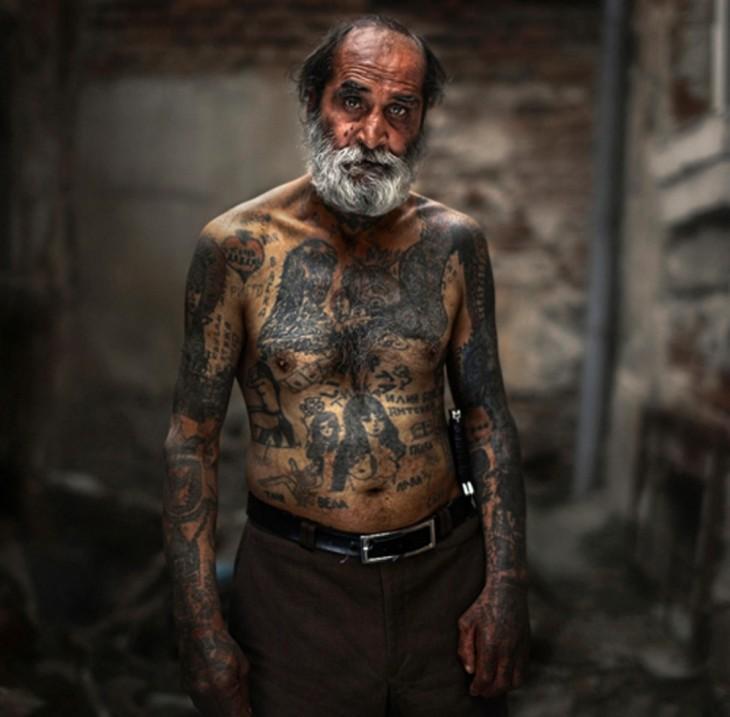 Hombre mayor sin camisa luciendo sus tatuajes del cuerpo