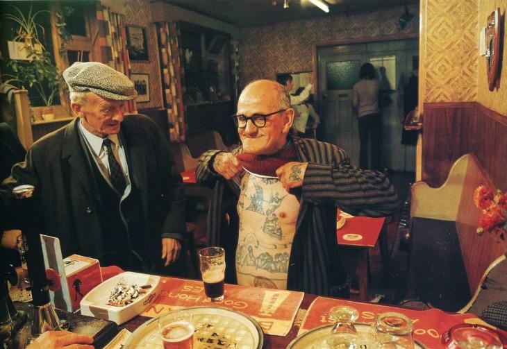 Hombre mayor enseñando sus tatuajes del cuerpo a otro adulto