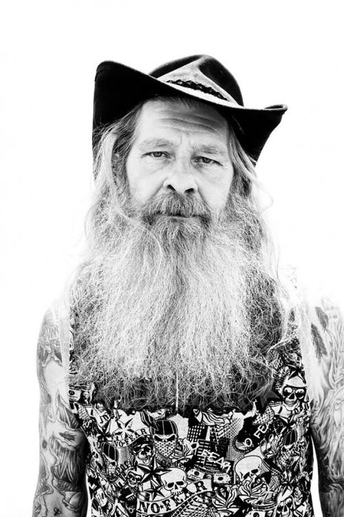Hombre con barba larga y sombrero enseñando los tatuajes de sus brazos
