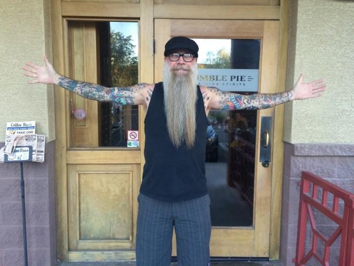 hombre mayor con barba larga y brazos tatuados