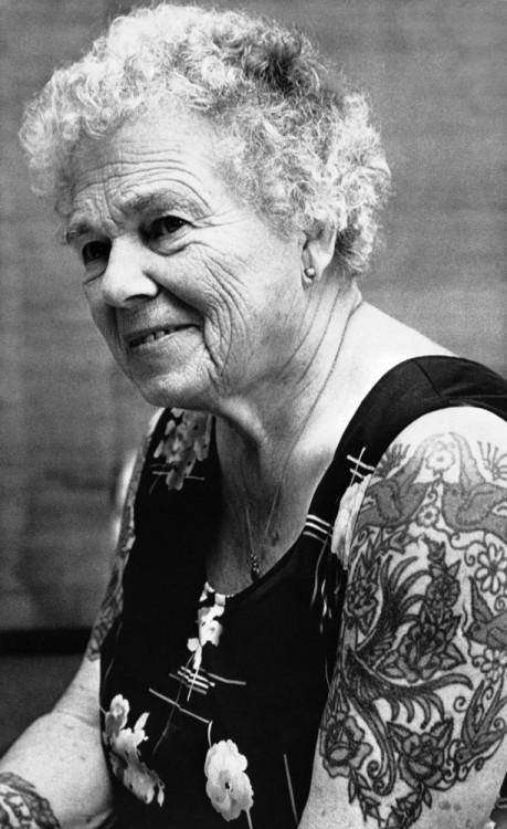 Mujer de edad adulta luciendo tatuajes en los brazos