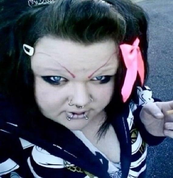 Cara de una chica con pircings en la boca y en la nariz y cejas en color rosa muy feas